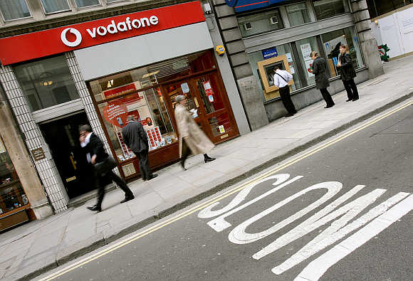 Passers-by walk past a Vodafone store in central London.