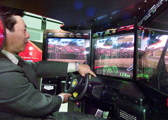 A man tries out Ferrari F355 Challenge racing car simulator developed by Japanese game maker Sega Enterprises in Tokyo.