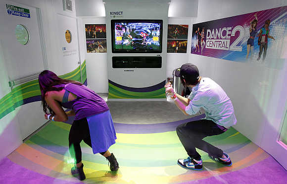 Attendees play the Dance Central 2 for the Xbox 360 Kinect in Los Angeles, California.