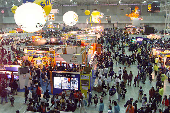 Children and their parents look over video game software at the World Hobby Fair in Makuhari, east of Tokyo, Japan.