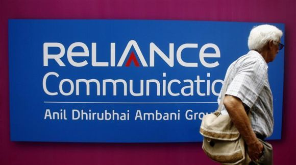A man walks past a logo of Reliance Communication before the Annual General Meeting in Mumbai.