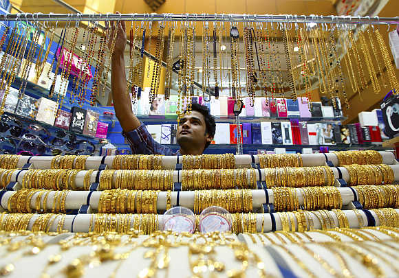 A salesman arranges jewellery at a shop at the gold souk in Dubai, United Arab Emirates.
