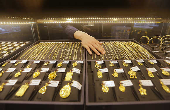 An employee arranges gold jewellery in the counter of a shop in Wuhan, Hubei province, China.