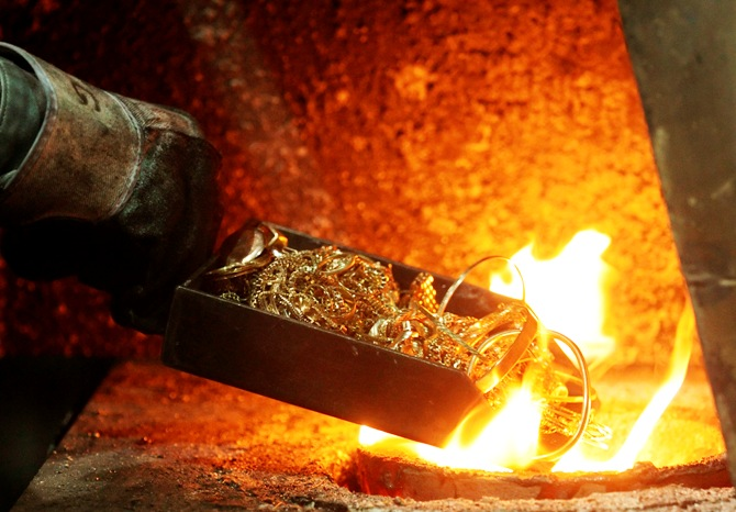 A worker places gold jewellery into a melting furnace.
