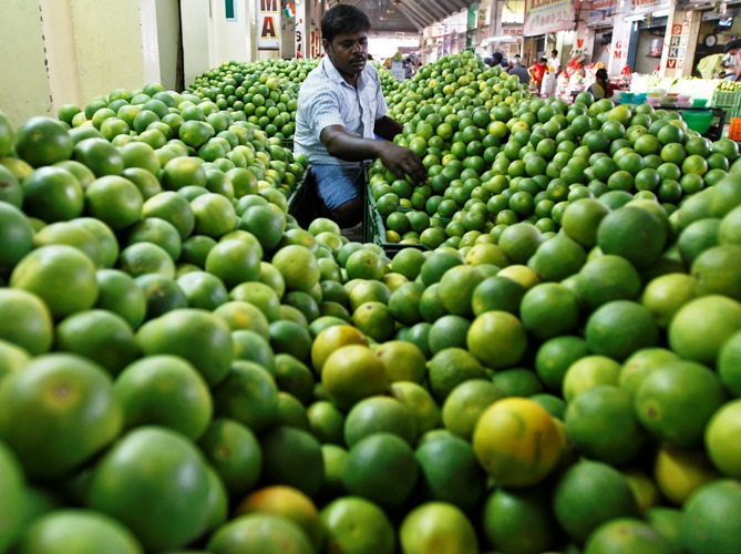 A vendor arranges sweet limes at his shop at a wholesale fruit market in Chennai.