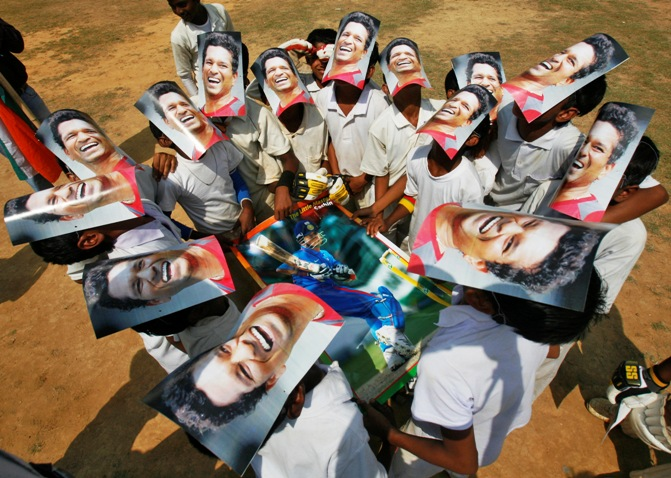 Boys from a local cricket academy wearing masks of Indian cricketer Sachin Tendulkar, celebrate his 100 international centuries in Agartala.