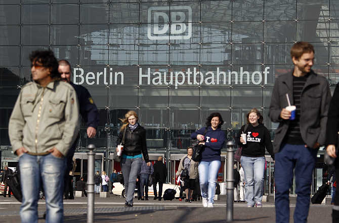 People walk in front of the main railway station Hauptbahnhof in Berlin, Germany.