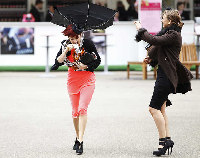 A racegoer struggles with her umbrella in strong winds at Royal Ascot, southwest of London, United Kingdom.