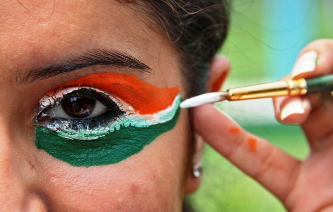 A college girl gets her eye painted in tri-colours of India's national flag.