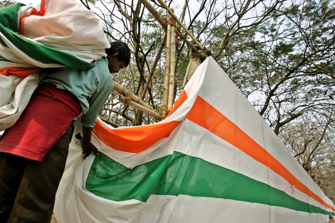 A labourer removes tri-coloured curtain after the Republic Day parade in Kolkata.