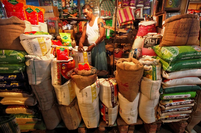 The owner of a kirana store arranges a rice sack in Kolkata.