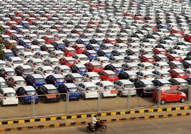 A man rides his motorbike past parked Hyundai cars ready for shipment at a port in the southern Indian city of Chennai.