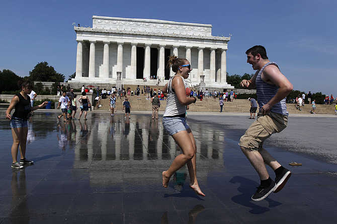 Karli Baumert, of Pryor, Oklahoma, left, and Max Cowdery, of Bremerton, Washington, right, dance underneath water sprinklers at the Lincoln Memorial to cool off during the punishing heat gripping Washington, DC, United States.