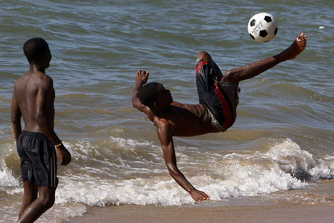 Boys play soccer at the beach in Benguela, Angola.
