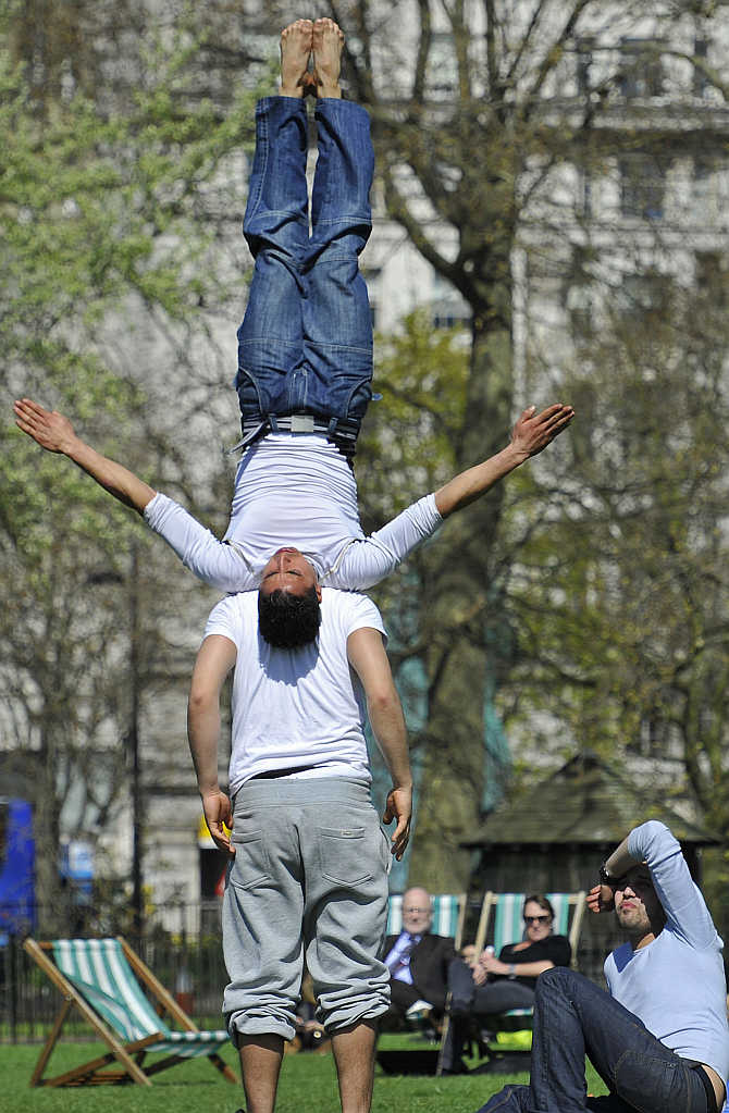 Park-goers practice gymnastic moves in Hyde Park in central London, United Kingdom.
