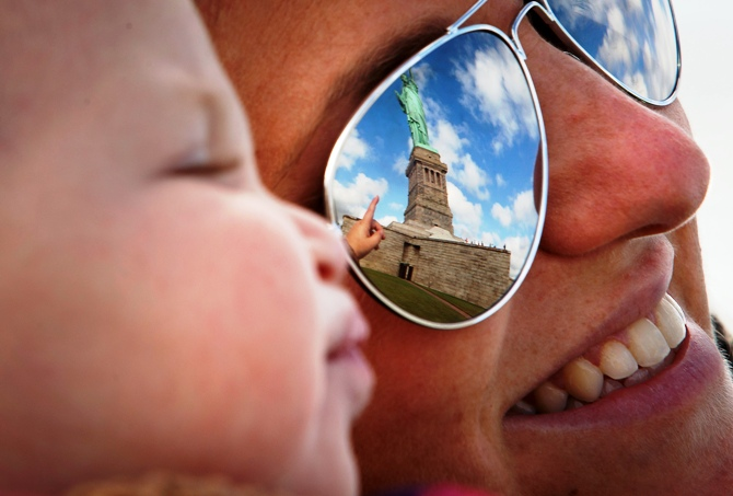 The Statue of Liberty is reflected in the glasses of Katie Ullman as she points to it while she holds her one-year-old son Tyler in her arms on Liberty Island in New York, October 13, 2013.