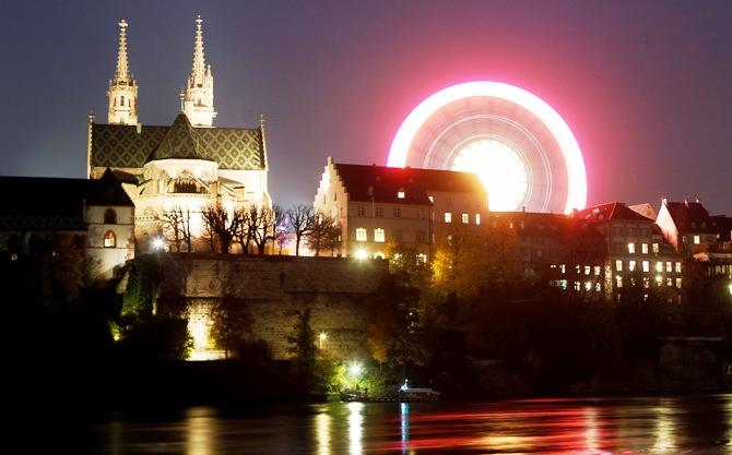 A long time exposure shows a ferris wheel turning beside Basel's landmark the Muenster church on the borders of the Rhine river.