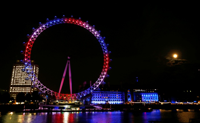 The London Eye is lit in red, white and blue and the full moon is visible after Catherine, Duchess of Cambridge gave birth   to a baby boy at St Mary's Hospital in central London, July 22, 2013.