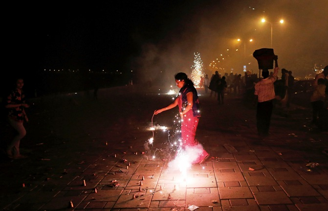 A woman lights firecrackers celebrating the Hindu festival of Diwali, the annual festival of lights, in Mumbai November 3, 2013.