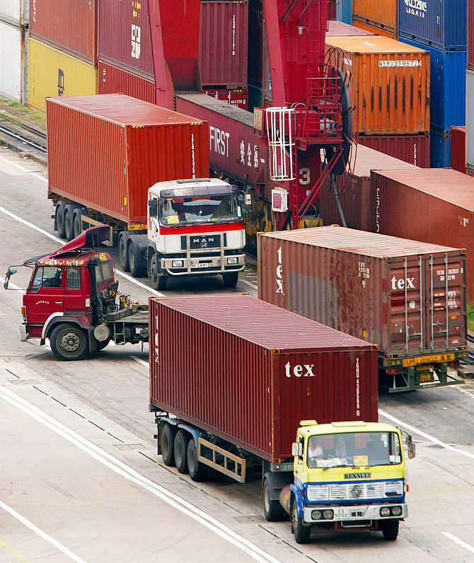 Loaded trucks leave a Hong Kong container terminal.