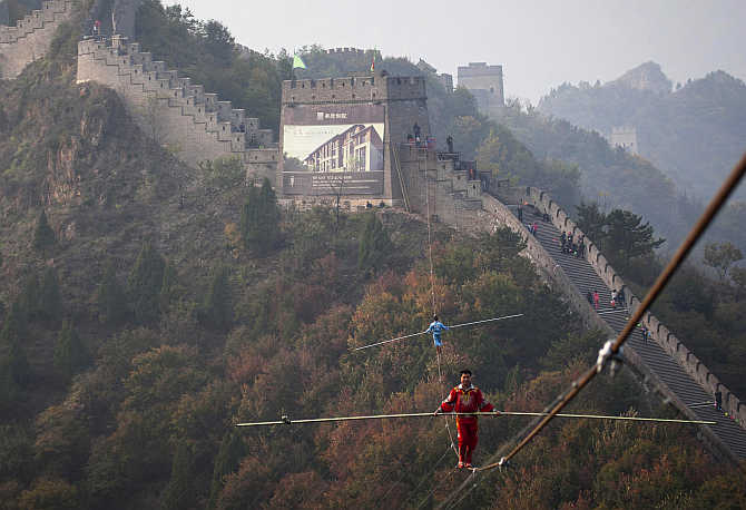 Adili Wuxor, front, who is known as 'Prince of the Tightrope', and his apprentice walk on a tightrope above the Great Wall in Tianjin, China.
