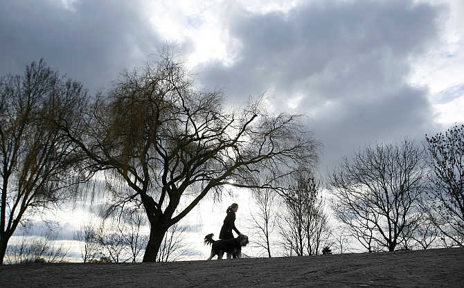 A woman walks with her dog on a dyke along the Weser River in Bremen, Germany.