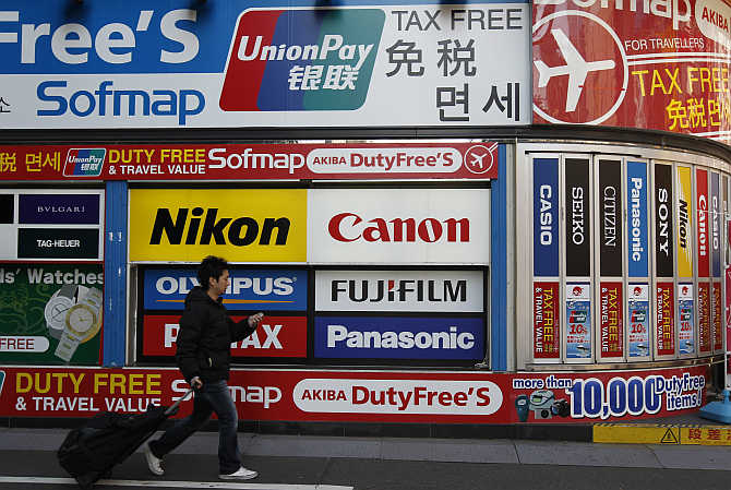 A man walks past an advertisement board at the electronic shopping district Akihabara in Tokyo, Japan.