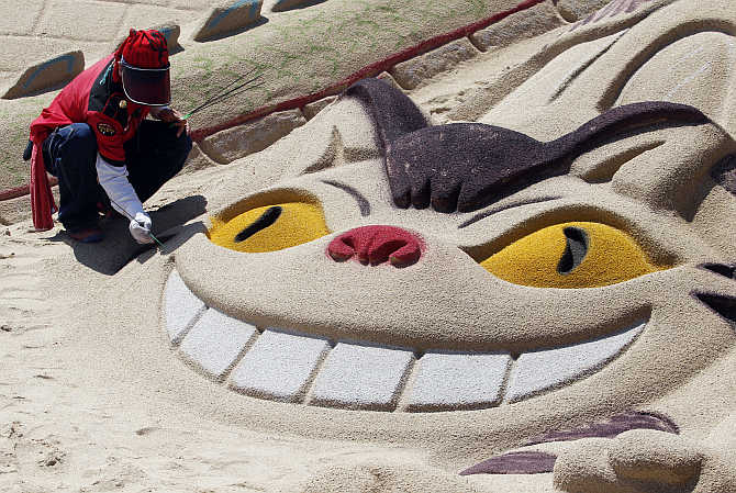 An artist adds finishing touches to a sand sculpture of a cat at the Haeundae Sand Festival in Busan, South Korea.