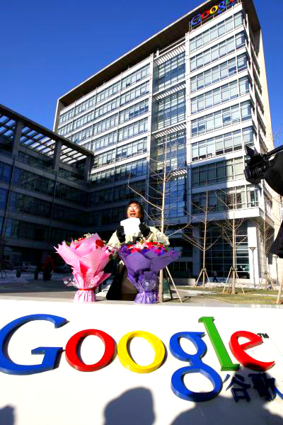 A Chinese Google user stands with bouquets of flowers that he wants to present to the Google China headquarters in Beijing.