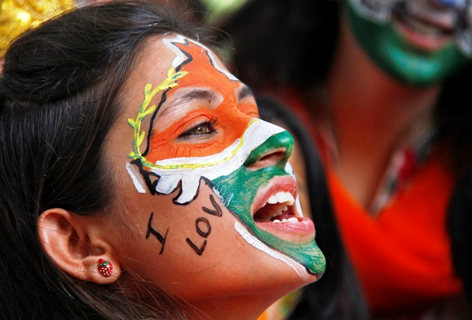 A girl, with her face painted in the colours of India's national flag, chants slogans as she takes part in a cultural program to celebrate India's Independence Day.