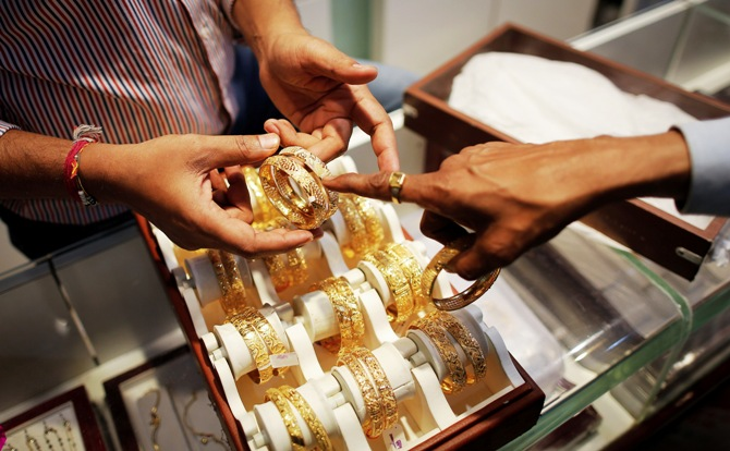An employee shows gold bangles to a customer at a jewellery showroom in Mumbai.