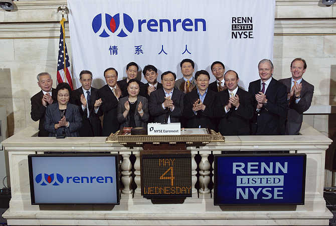 China's Renren Chairman and Chief Executive Officer, Joseph Chen, centre, is joined by executives and guests as he rings the opening bell at the New York Stock Exchange.