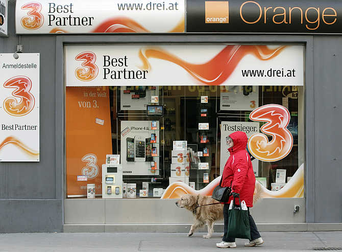 A woman and her dog walk by a telecommunications store advertising Orange in Vienna, Austria.