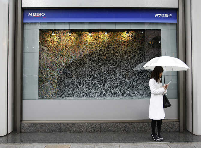 A woman stands under an umbrella outside a Mizuho bank branch in Tokyo.