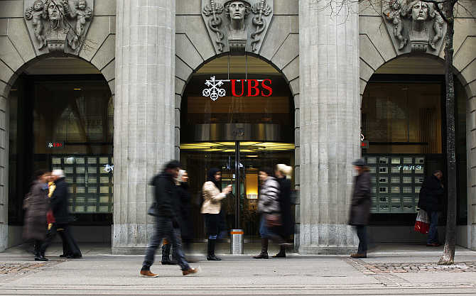 People walk in front of a branch of Swiss bank UBS in Zurich.