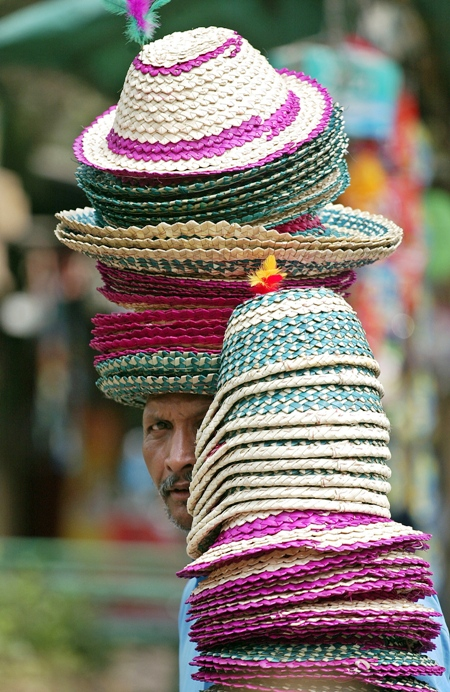 A hawker sells straw hats in Kolkata.