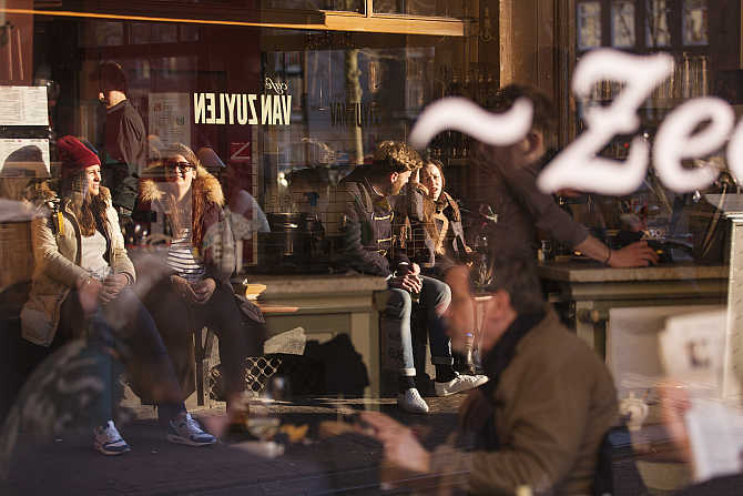 Visitors of a local cafe are reflected in a window in Amsterdam, the Netherlands.