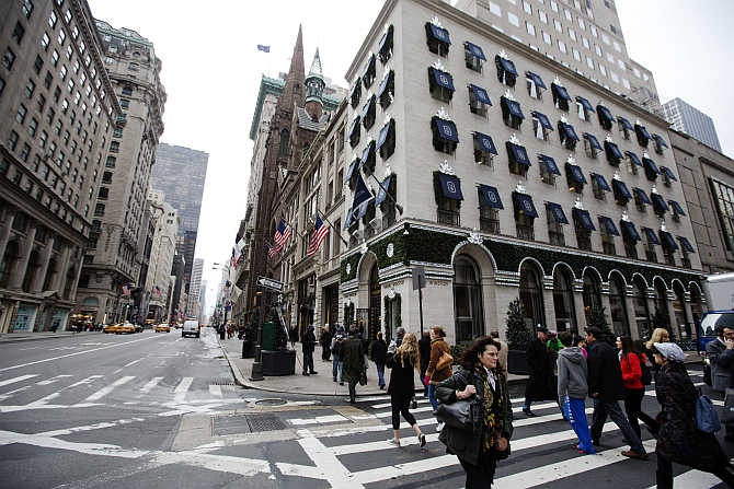 Pedestrians walk past the Harry Winston jewellery store, right, on 5th Avenue in New York, United States.