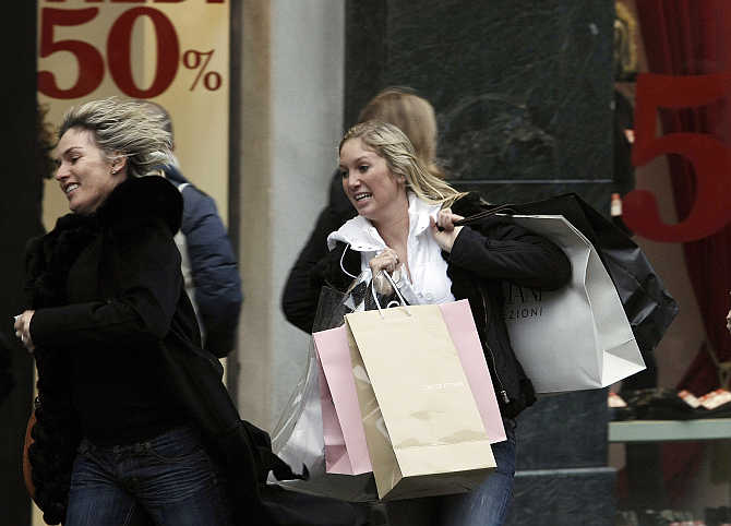 Women runs past a clothing boutique announcing its New Year sales in Milan, Italy.