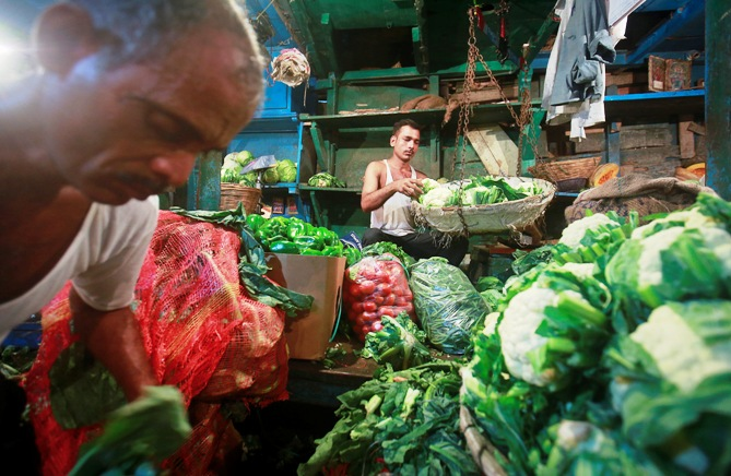 A vendor weighs vegetables as another sorts them at their stall at a wholesale food market in Mumbai.
