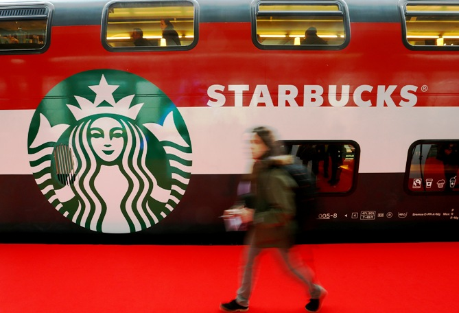 A woman walks past a Starbucks logo painted on a railway coach at the main train station in Zurich.