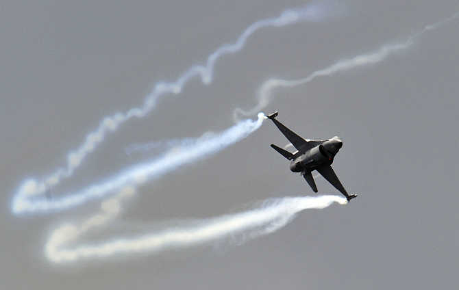 A General Dynamics F-16 Fighting Falcon fighter jet performs during an air display at the Farnborough Airshow in Farnborough, England.