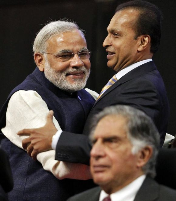 Gujarat's chief minister Narendra Modi (L) and Anil Ambani, chairman of Anil Dhirubhai Ambani Group, embrace as Ratan Tata, chairman Emeritus of Tata group, looks on during the inauguration ceremony of the Vibrant Gujarat global investor summit.