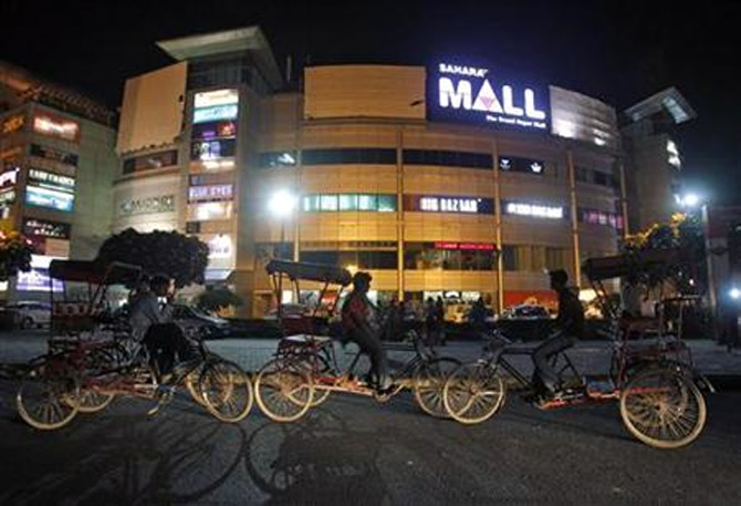 Rickshaw pullers wait for customers outside the Sahara Mall, a shopping centre built by Sahara group, in Gurgaon.