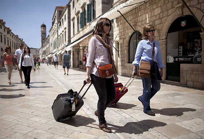 Tourists pull their luggage as they walk on Stradun street in Croatia's Unesco protected medieval town of Dubrovnik.