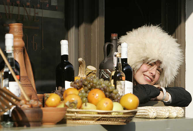 A shop assistant wearing a Georgian traditional hat smiles as she sells wine and fruit during the Tbilisoba city day celebration in Tbilisi, Georgia.