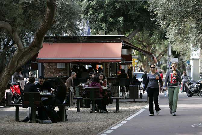 People walk past a cafe in Tel Aviv, Israel.