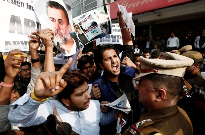 Activists of the Akhil Bharatiya Vidyarthi Parishad, linked to Bharatiya Janata Party, hold posters of Tarun Tejpal and shout slogans as police try to stop them during a protest in New Delhi November 22, 2013.
