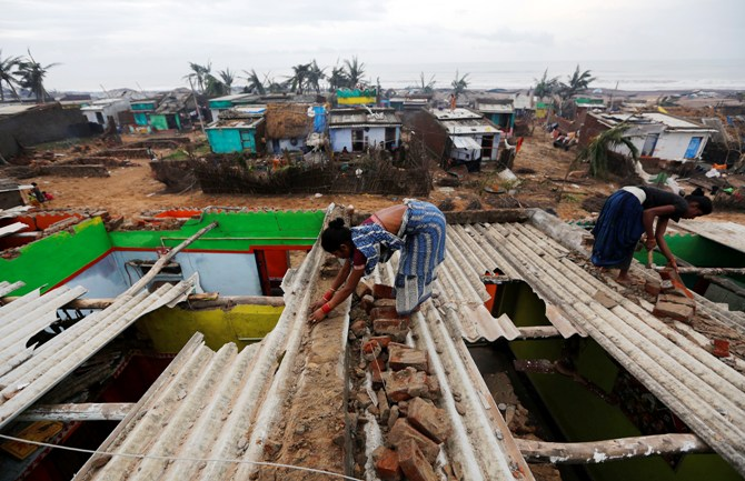 Women repair the roof of their houses at the cyclone-hit Nalianuagaon village in Ganjam district, Orissa.