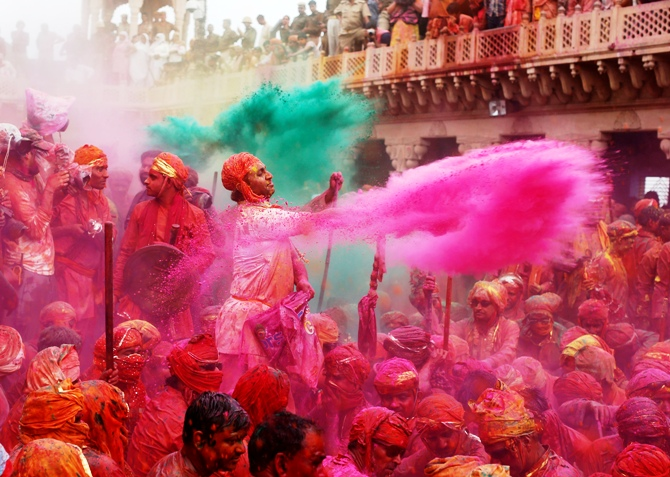 People throw coloured powder as they celebrate 'Lathmar Holi' at Nandgaon village in Uttar Pradesh.